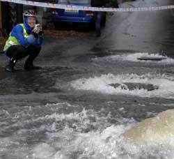 Roar Hansen fotograferer regnvannet som kommer opp av kumlokkene på Laksevåg i et skikkelig regnvær i oktober 2007.