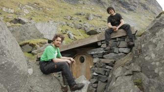 Jørn N. Ranum (23) og Inge Wegge (25) bygde huset sitt mellom fjellveggen og en stor stein. Huset ble bygget av drivved de fant på stranda.