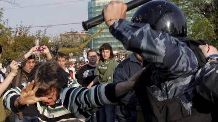 Opprørspolitiet slår løs på demonstrantene.