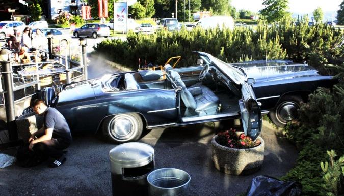 Drive in er dessverre ikke et av tilbudene på uteserveringen i Skedsmo - så da denne digre, amerikanske bil kom kjørende gjennom hekken var det mange som fikk store øyne. FOTO: Maria Schiller Tønnesen, Romerikes Blad