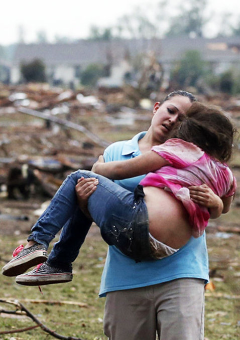 A woman carries a child through a field near the collapsed Plaza Towers Elementary School in Moore, Okla., Monday, May 20, 2013. The relationship between the woman and the child was not immediately known. A tornado as much as half a mile (.8 kilometers) wide with winds up to 200 mph (320 kph) roared through the Oklahoma City suburbs Monday, flattening entire neighborhoods, setting buildings on fire and landing a direct blow on an elementary school. (AP Photo Sue Ogrocki)